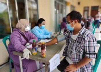 Salah seorang warga sedang dilkukan proses screening oleh tim nakes sebelum menerima vaksin. (foto;dok)
